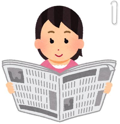 新聞を広げて読む女性